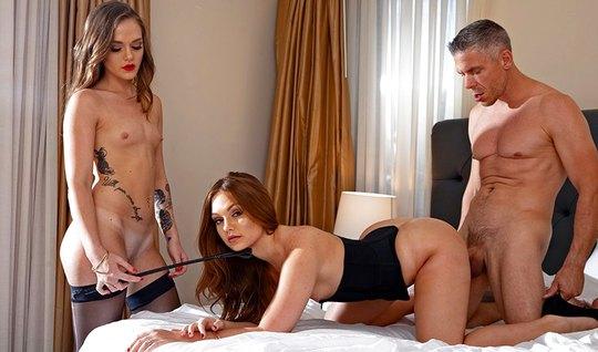 Две молодые девушки и один мужчина в спальне занимаются групповым сексом